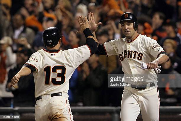 Cody Ross and Pat Burrell of the San Francisco Giants celebrate after scoring on a double by Pablo Sandoval in the sixth inning of Game Four of the...