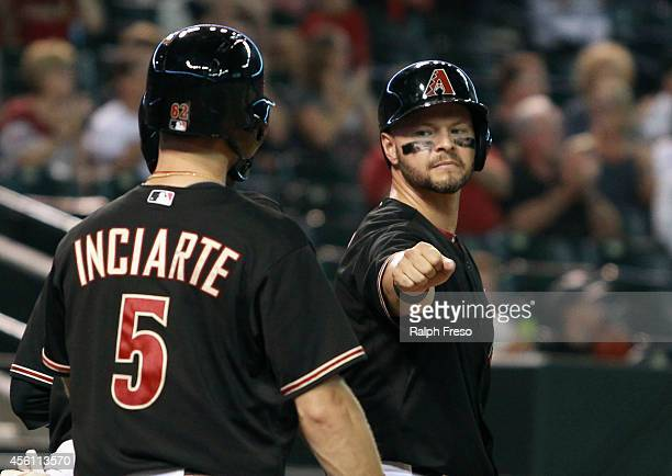 Cody Ross of the Arizona Diamondbacks fist bumps teammate Ender Inciarte after scoring a run against the San Diego Padres during the seventh inning...