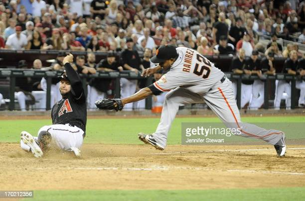 Cody Ross of the Arizona Diamondbacks successfully slides into home plate against pitcher Ramon Ramirez of the San Francisco Giants in the sixth...