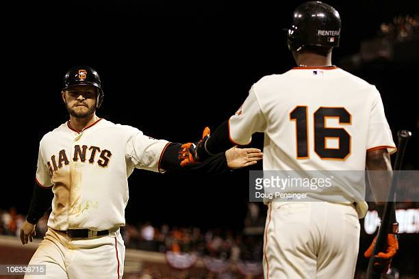 Cody Ross of the San Francisco Giants celebrates scoring a run in the seventh inning with Edgar Renteria while taking on the Texas Rangers in Game...