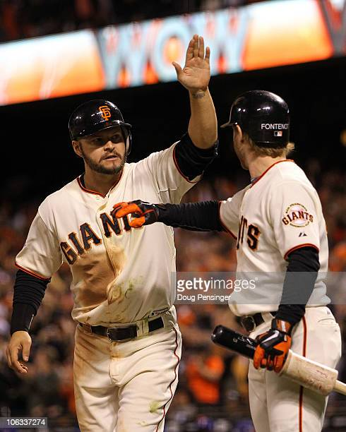 Cody Ross of the San Francisco Giants celebrates scoring a run with teammate Mike Fontenot in the eighth inning while taking on the Texas Rangers in...