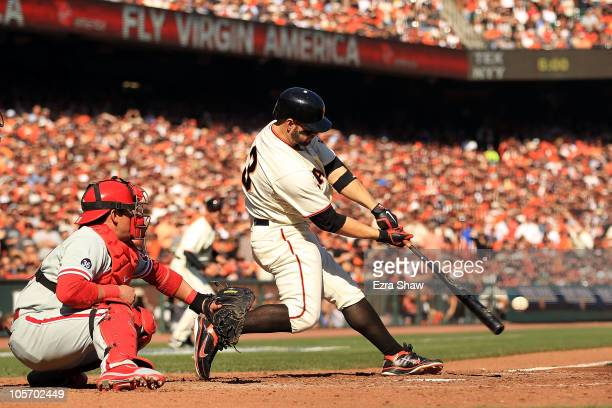 Cody Ross of the San Francisco Giants hits an RBI single against Cole Hamels of the Philadelphia Phillies in the fourth inning of Game Three of the...