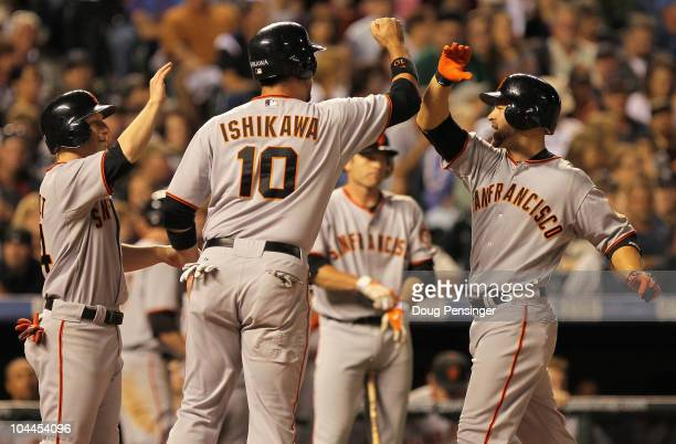 Cody Ross of the San Francisco Giants is welcomed home by Travis Ishikawa and Mike Fontenot who scored on his three run home run off of Esmil Rogers...