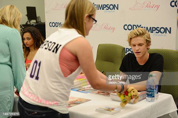 Cody Simpson recieves a gift from a fan during a meet and greet at Genesco Park on August 2 2012 in Nashville Tennessee