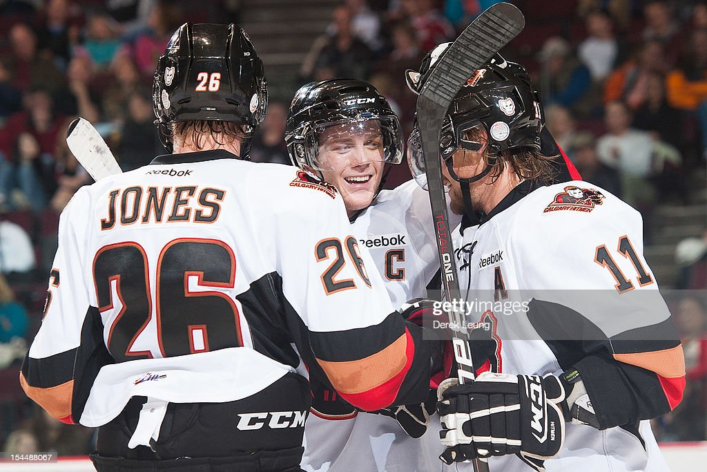 Cody Sylvester #16 congratulates Brooks Macek #11 of the Calgary Hitmen for scoring the Hitmen's fifth goal of the game against Tyler Fuhr #31 (not pictured) of the Vancouver Giants in WHL action on October 20, 2012 at Pacific Coliseum in Vancouver, British Columbia, Canada.