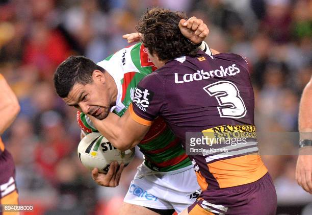 Cody Walker of the Rabbitohs is tackled by James Roberts of the Broncos during the round 14 NRL match between the Brisbane Broncos and the South...