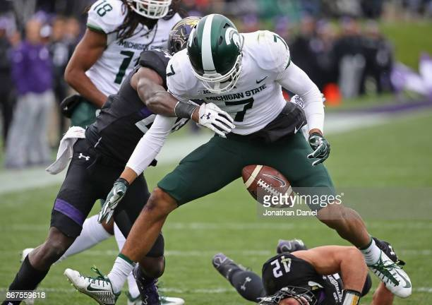 Cody White of the Michigan State Spartans fumbles the ball as he's hit by Montre Hartage of the Northwestern Wildcats at Ryan Field on October 28...