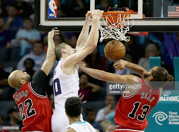 Cody Zeller of the Charlotte Hornets dunks the ball against teammates Taj Gibson and Joakim Noah of the Chicago Bulls during their game at Time...