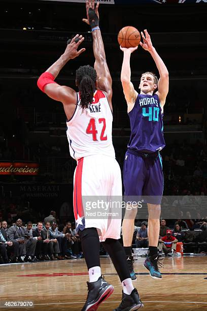 Cody Zeller of the Charlotte Hornets shoots against Nene Hilario of the Washington Wizards on February 2 2015 at the Verizon Center in Washington DC...