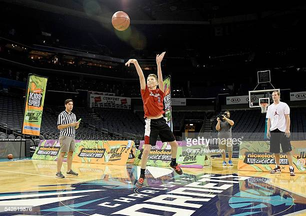 Cody Zeller of the Charlotte Hornets watches Camden Johnson make a halfcourt shot during tryouts for the 'Triple Shot Challenge Kids' Choice Sports...