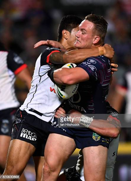 Coen Hess of the Cowboys is tackled by Mafoa'aeataHingano of the Warriors during the round 20 NRL match between the North Queensland Cowboys and the...