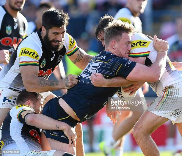 Coen Hess of the Cowboys is wrapped up by the Panthers defence during the round 16 NRL match between the North Queensland Cowboys and the Penrith...