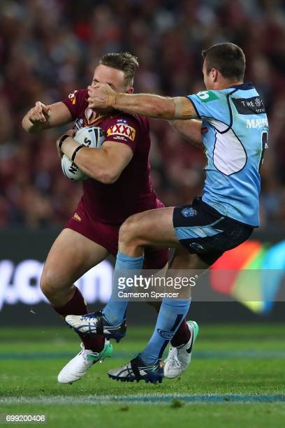 Coen Hess of the Maroons is tackled by James Maloney of the Blues during game two of the State Of Origin series between the New South Wales Blues and...