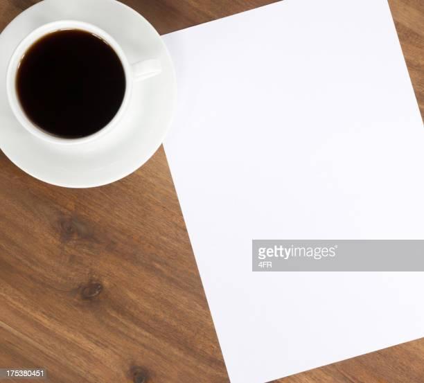 Kaffee und leeres Papier mit Textfreiraum auf dem Schreibtisch