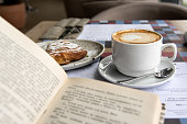 Still life details, cup of Cappuccino and cake with book on table in coffee shop cafe, shallow DOF.