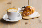 Coffee and Croissant on a wooden table with soft background