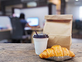 coffee and croissant with paper bag on wooden table over office blurred background