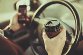 Stylish driver with a smartphone in hand and paper cup of hot coffee in the driver's seat. The concept of inattention at the wheel, rest, coffee break to cheer.