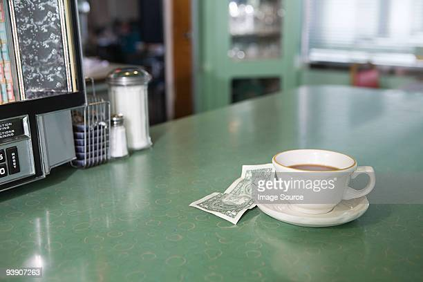 Coffee and money on a diner counter