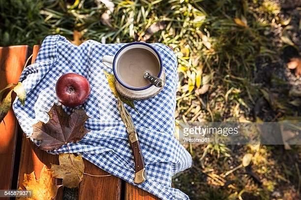 Coffee, apple and autumn leaves on wooden bench