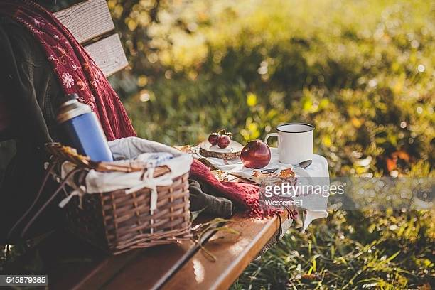 Coffee, apple, grapes and autumn leaves on wooden bench