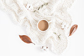 Autumn or winter composition. Cup of coffee, dried autumn leaves, knitted blanket on white background. Flat lay, top view