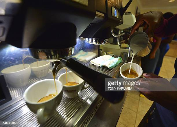 A coffee barista shows how to pour milk in a coffee in what is commonly known as 'latte art' or 'coffee art' at Dormans cafe in Nairobi on April 25...