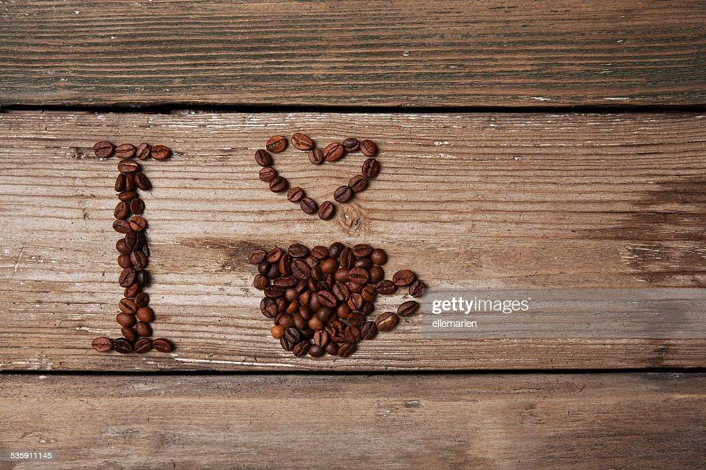 Grãos de café e o copo com coração em fundo de madeira : Foto de stock