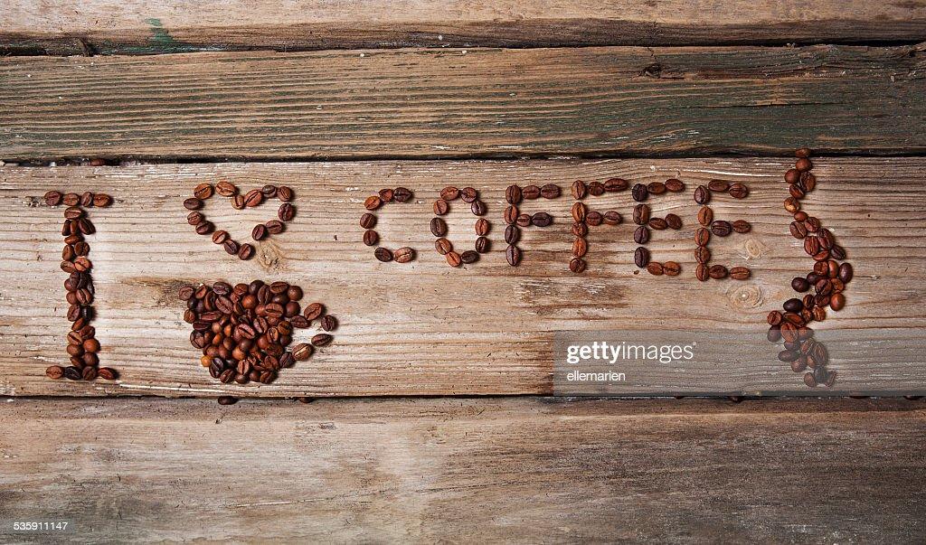 Taza de granos de café y con corazón sobre fondo de madera : Foto de stock