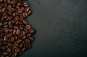 Roasted brown coffee beans on the black concrete stone background. Flatlay style, messy pattern.