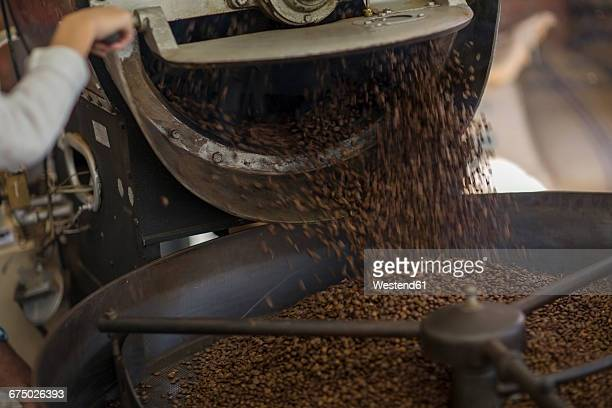 Coffee beans being poured in cooling cylinder