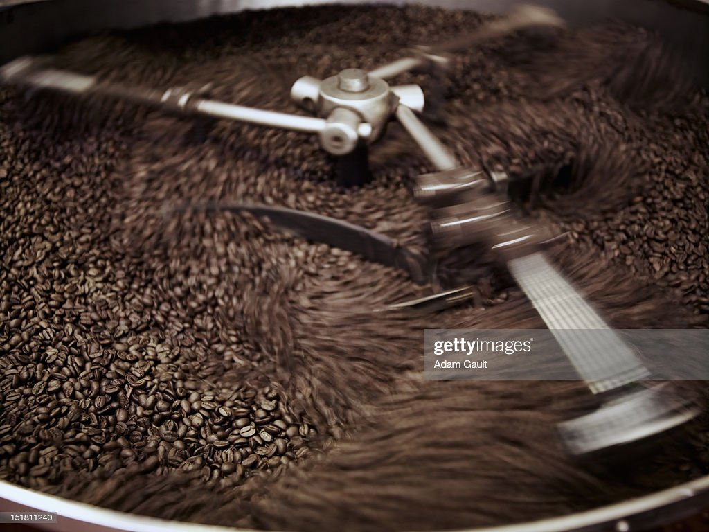 Coffee beans being processed in roasting machine : Stock Photo