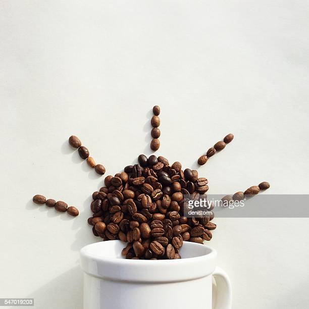Coffee beans coming out of a cup in the shape of the sun