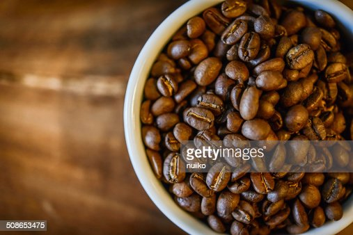 Coffee beans in cup on grunge wooden background : Stock Photo