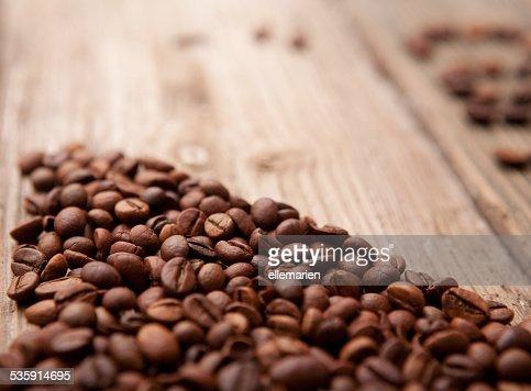 Grãos de café sobre fundo de madeira : Foto de stock