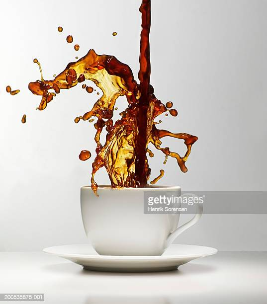 Coffee being poured splashing in cup