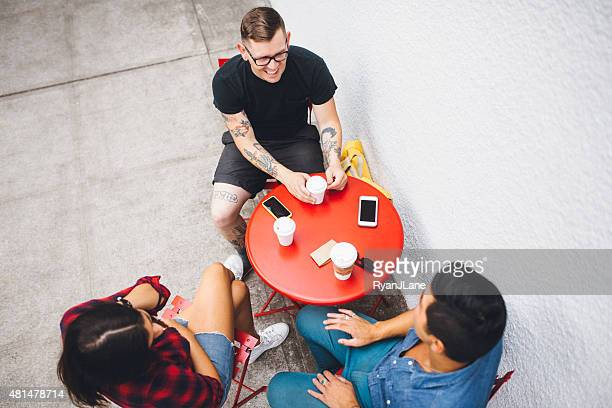 Coffee Break For Friends With Smart Phones In Urban Setting