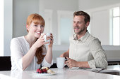 Couple enjoying coffee and a snack in their kitchen