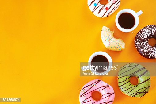 Coffee break with assorted donuts on yellow table with copy space. : Stock Photo
