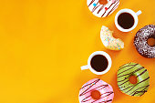Pistachio, chocolate, vanilla, strawberry donuts and two cups of espresso over yellow background.