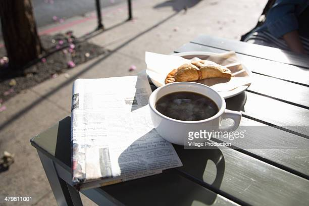 Coffee, breakfast pastry and newspaper on table