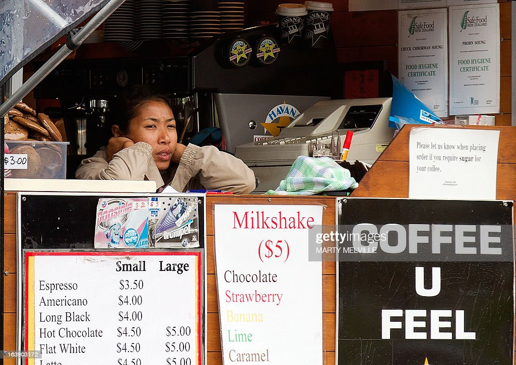 A coffee card retailer waits as rain halts play during day five of the international cricket Test match between New Zealand and England played at the Basin Reserve in Wellington on March 18, 2013. AFP PHOTO / Marty MELVILLE