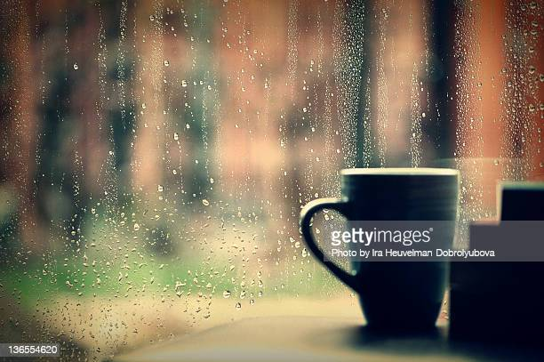 Coffee cup and books against rainy window