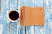 Coffee cup and notebook with to do list, planning concept