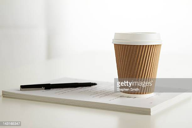 coffee cup and pen on table in office