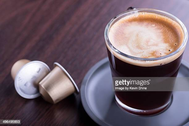 Coffee cup and two pods on table