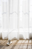 Coffee cup by net curtains