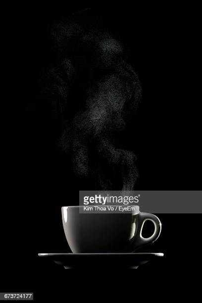 Coffee Cup In Plate Against Black Background