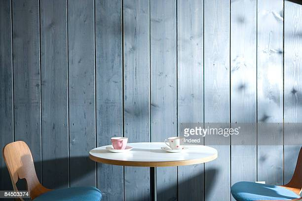 Coffee cup on cafe table and chair