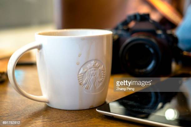 Coffee cup on table while the customer has a break in a Starbucks shop In the second quarter of 2017 Starbucks opened its stores to five new cities...